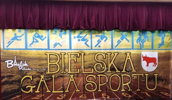 """Ilustracja przedstawia zółty napis: """"Bielska Gala Sportu"""", logotyp """"Bielsk Podlaski łączy ludzi"""" i herb miasta Bielsk Podlaski oraz znaki symbolizujące różne dyscypliny sportowe"""