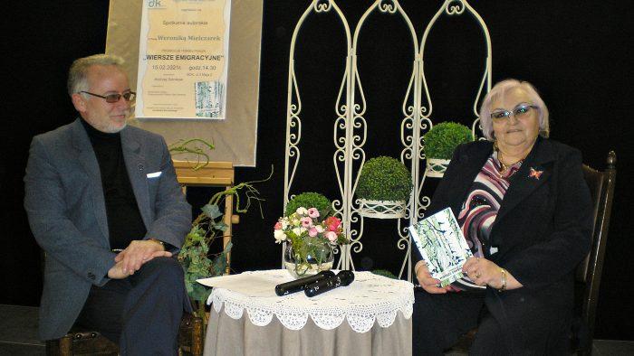 Ilustracja przedstawia dwie osoby siedzące na krzesłach przy stoliku przykrytym białym obrusem. Na stole stoi wazon z bukietem kwiatów i leżą dwa mikrofony. Po prawej stronie siedzi autorka ksiązki Weronika Mielczarek, po lewej - prowadzący spotkanie Andrzej Salnikow.
