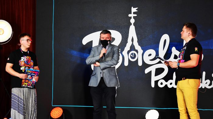 """ilustracja przedstawia trzy osoby na scenie finału Orkiestry: po bokach prowadzących aktorów, po środku burmistrza mówiącego do mikrofonu. W tle biały napis na czarnym tle - logotyp """"Bielsk Podlaski łączy ludzi""""."""