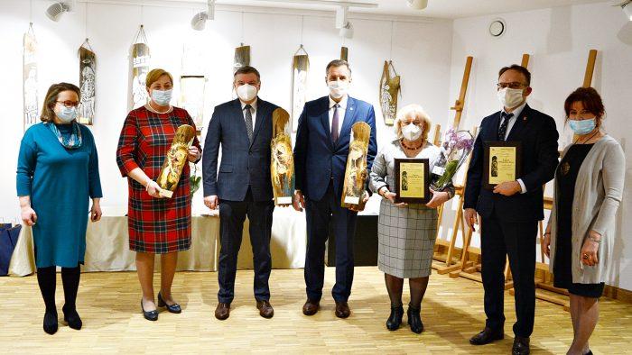 Ilustracja przedstawia siedem osób stojących w rzędzie, trzymających w rękach drewniane rzeźby - nagrody. Są to osoby nagrodzone, a po bokach stoją dyrektor i kierownik domu kultury. W tle widać wnętrze galerii Bielskiego Domu Kultury.