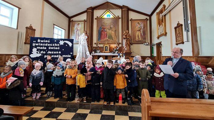 """ilustracja przedstawia wnętrze kościoła wypełnionego ludźmi. Na pierwszym planie stoją dzieci uczestniczące w konkursie, a po prawej stronie organizator konkursu ksiądz Zbigniew Karolak przemawiający do mikrofonu i trzymający kartkę papieru. W tle zdobiony ołtarz kościelny oraz niebieska tablica z białymi literami tworzącymi napis: """"Świeć Gwiazdeczko Mała Świeć do Jezuska Prowadź Mnie""""."""