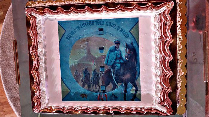 ilustracja przedstawia leżące na stole ciasto - tort z wizerunkiem muralu. Na muralu widać mężczyzn w mundurach i z szablami na koniach, a w tle wierzę ratusza.