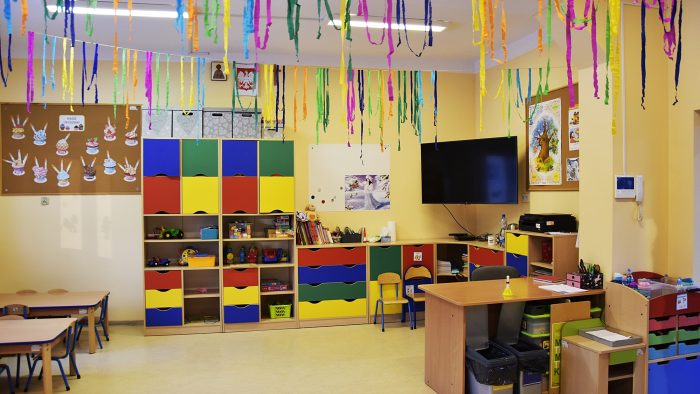 Ilustracja przedstawia wnętrze wyremontowanej klasy lekcyjnej. Na środku kadru kolorowe szafki z zabawkami, po lewej stronie tablica korkowa, po prawej stronie wiszący telewizor. Na białym suficie dwie świecące się lampy i zwisające kolorowe ozdoby z papieru. Na podłodze stoły, krzesła i po prawej stronie biurko.