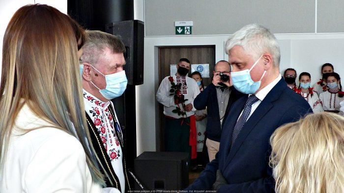 Na zdjęciu Wojewoda Podlaski Bohdan Paszkowski (stoi z prawej) wręcza medal Sergiuszowi Łukaszukowi. W tle stoją członkowie zespołu Małanka ubrani w stroje ludowe.