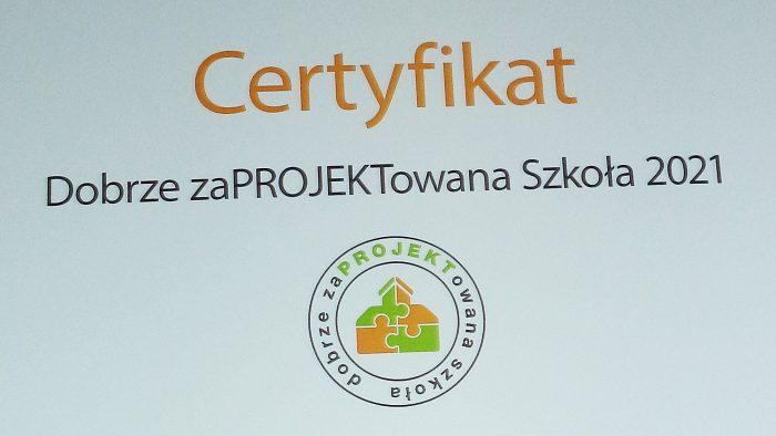 """ilustracja przedstawia fragment dokumentu z napisem: """"Certyfikat - Dobrze Zaprojektowana Szkoła"""" oraz logotyp logotyp składający się z domku zbudowanego z czterech różnokolorowych puzzli oraz okalający go napis: """"dobrze zaprojektowana szkoła""""."""