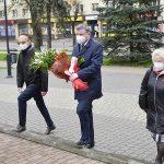 zdjęcie przedstawia trzy osoby: w środku burmistrz niosący wiązankę biało-czerwonych kwiatów, po prawej wiceburmistrz, po lewej wicestarosta