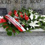 zdjęcie przedstawia biało-czerwony wieniec kwiatów z szarfą leżący na pomniku