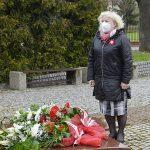 zdjęcie przedstawia panią wiceburmistrz stojącą przed pomnikiem, przed którym leżą złożone kwiaty