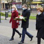 zdjęcie przedstawia trzy osoby przed pomnikiem podczas składania kwiatów: w środku dyrektor szkoły niosący wiązankę kwiatów, po bokach nauczycielki