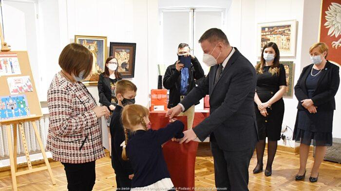 Ilustracja przedstawia wnętrze muzeum w ratuszu. Na pierwszym planie burmistrz wręcza nagrody i upominki dwojgu dzieci, za którymi stoi dorosła opiekunka. W tle widać innych uczestników uroczystości, w tym mężczyznę robiącego zdjęcie telefonem komórkowym.