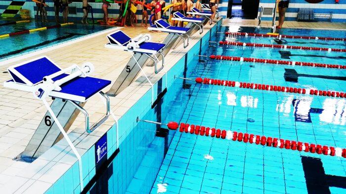 Ilustracja przedstawia wnętrze pływalni. Po lewej stronie niebielskie platformy startowe dla zawodników, zakupione w ramach projektu, po prawej - tory wodne, z nowymi torami je wydzielającymi.