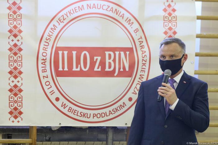 Zdjęcie przedstawia prezydenta Andrzeja Dudę przemawiającego do mikrofonu trzymającego w ręce, na tle biało-czerwono-białego logotypu II Liceum Ogólnokształcącego w Bielsku Podlaskim.