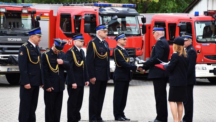 Ilustracja przedstawia grupę strażaków w strojach galowych, ustawionych w szeregu na tle wozów bojowych. Z prawej jeden z komendantów wojewódzkich wręcza strażakowi awans i dyplom, ściskając mu dłoń. Za nim stoi komendant powiatowy i strażaczka.