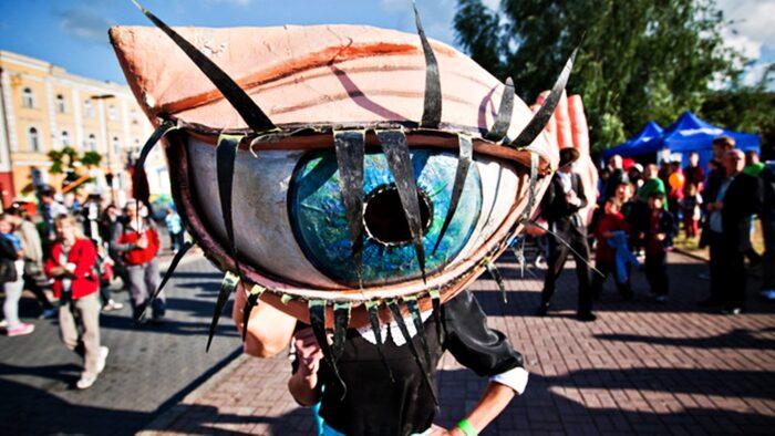 Ilustracja przedstawia przebranego aktora na miejskiej ulicy. Aktor ucharakteryzowany jest na wielkie oko z rzęsami. Wokół aktora przechadzają się ludzie.