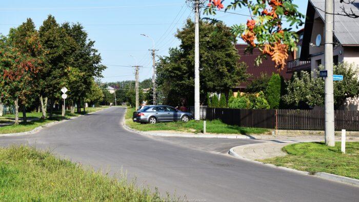 Ilustracja przestawia skrzyżowanie ulic: Kowalskiej i Sikorskiego. Skrzyżowanie otacza zabudowa jednorodzinna, zieleń ogrodów, drzewa i słupy oświetleniowe.