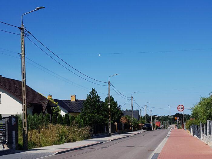Na zdjęciu widoczny jest odcinek ulicy Warzywnej. W lewej części zdjęcia znajdują się słupy oświetlenia ulicznego wraz z nowymi oprawami LED. W oddali zlokalizowane są posesje prywatne. Środkowa i prawa część zdjęcia przedstawia jezdnię o nawierzchni asfaltowej oraz ścieżką rowerową z kostki brukowej w kolorze pomarańczowym. Zdjęcie wykonano przy słonecznej pogodzie i bezchmurnym niebie.