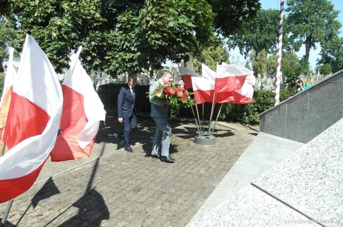 Zdjęcie przedstawia burmistrza składającego wieniec przed pomnikiem Pamięci Narodowej, podczas uroczystości Święta Wojska Polskiego. Burmistrz niesie wieniec, a za nim kroczy przewodniczący rady miasta. Po bokach łopocą biało-czerwone flagi na stojakach. W tle dziennikarz robi zdjęcie aparatem fotograficznym.