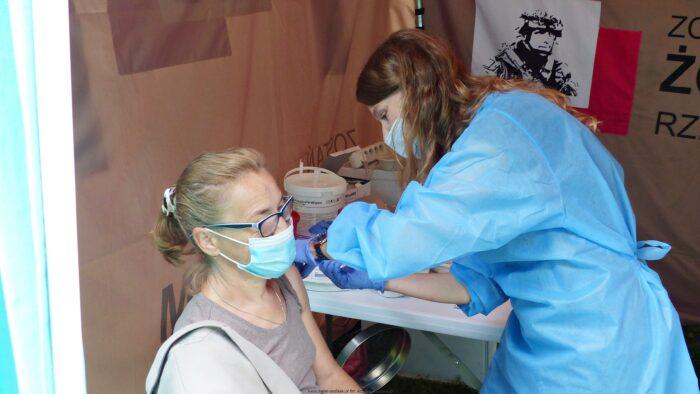 Ilustracja przedstawia dwie osoby znajdujące się w przenośnym punkcie szczepień. Z lewej siedzi szczepiona kobieta w maseczce. Z prawej stoi szczepiąca pielęgniarka w niebieskim fartuchu, maseczce i rękawicach.