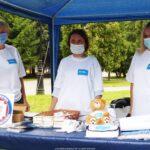 Zdjęcie z akcji promującej szczepienia. Przedstawia trzy przedstawicielki sanepidu, ubrane w białe fartuchy i z maseczkami na twarzach, stojące za stołem z gadżetami promocyjnymi.