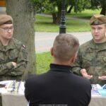 Zdjęcie z akcji promującej szczepienia. Przedstawia dwóch żołnierzy w mundurach za stołem z gadżetami promocyjnymi. Na środku kadru stojący tyłem mężczyzna ubrany na czarno, rozmawiający z żołnierzami.
