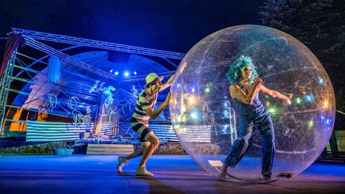 Ilustracja przedstawia kadr z jednego z wertepowych spektakli. Na tle amfiteatru miejskiego w Bielsku Podlaskim widać dwoje aktorów. Z prawej tańczącą kobietę w niebielskiej peruce, w wielkiej plastikowej bańce, z prawej mężczyznę w pasiastym stroju i żółtym kapeluszu, pchającego plastikową kulę z kobietą.