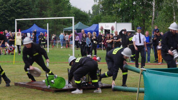 ilustracja przedstawia strażaków podczas zmagań w zawodach