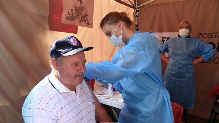 Ilustracja przedstawia mężczyznę szczepionego przez ubraną w maseczkę i fartuch pielęgniarkę.