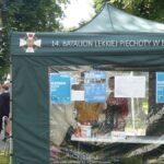 Ilustracja przedstawia kadr z drugiego dnia prowadzonych szczepień. Widać na niej namiot z plakatami i ludzi czekających na szczepienie.