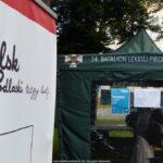 Ilustracja przedstawia kadr z drugiego dnia prowadzonych szczepień. Widać na niej baner z logotypem miasta i namiot z plakatami.