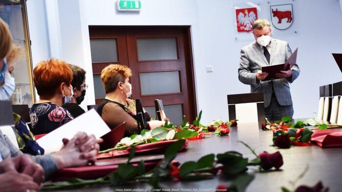 Ilustracja przedstawia burmistrza stojącego za stołem konferencyjnym oraz nauczycieli siedzących przy stole. Na stole leżą czerwone róże i dyplomy w okładkach.
