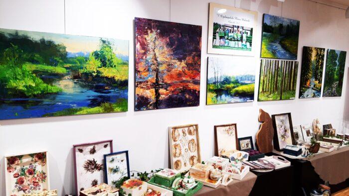 Ilustracja przedstawia wnętrze galerii sztuki BDK. Na ścianie wiszą obrazy, na stojącym pod nimi stole ustawione są inne kolorowe prace plastyczne.